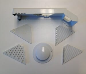 """My mandoline slicer comes with an assortment of interchangeable attachments, which vary the type of slices you get from it, plus a finger-saving """"handle"""" for when you get to the end of whatever it is you're slicing."""