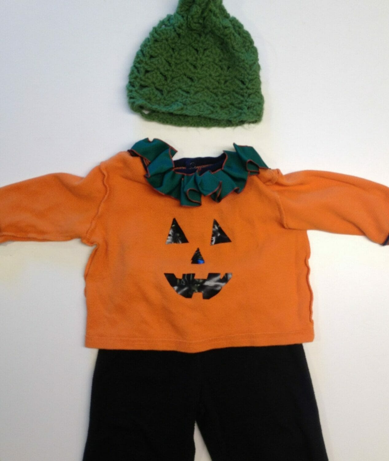 All you need to make a jack-o-lantern Halloween costume is an orange long-sleeve Tshirt, some black pants, black felt or tape, and scissors; the green ribbon collar and hand-crocheted hat are optional.
