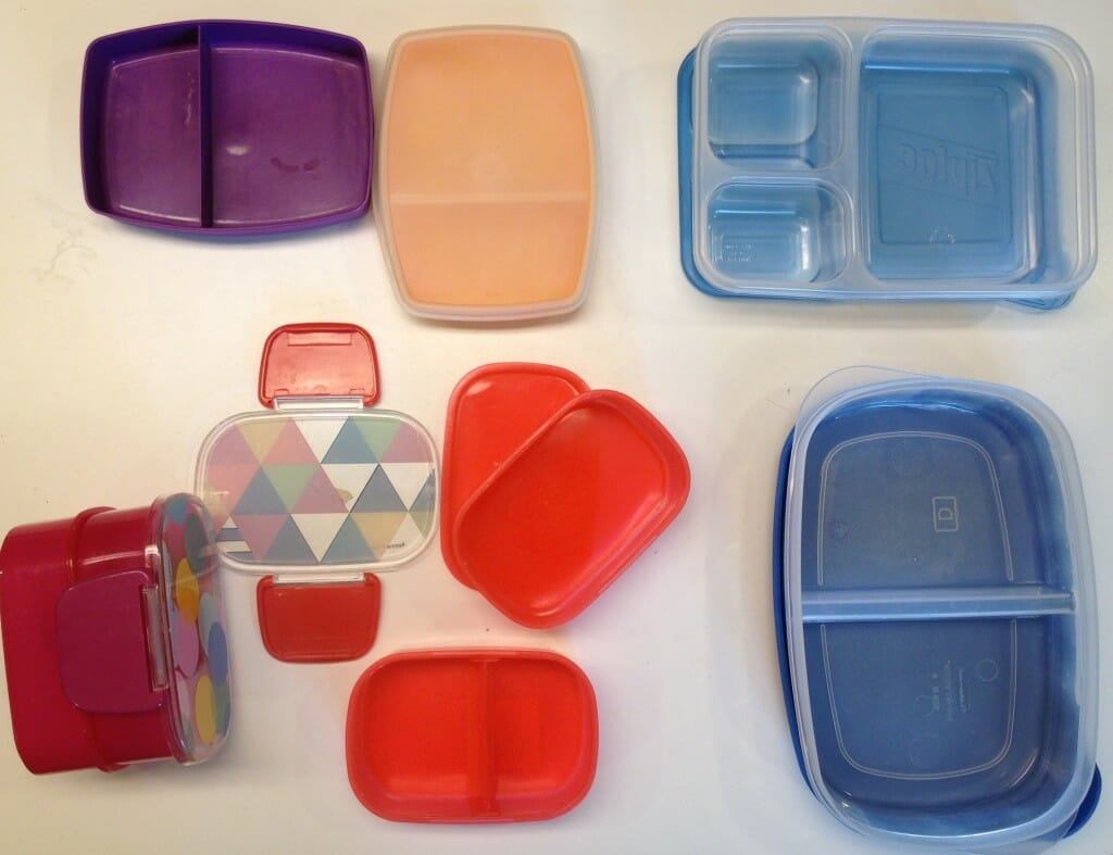 "Clockwise from upper left: our two Tupperware snack boxes, our Ziploc compartmentalized container, our Rubbermaid divided Serving Saver, and our two Target ""tiffin boxes."""