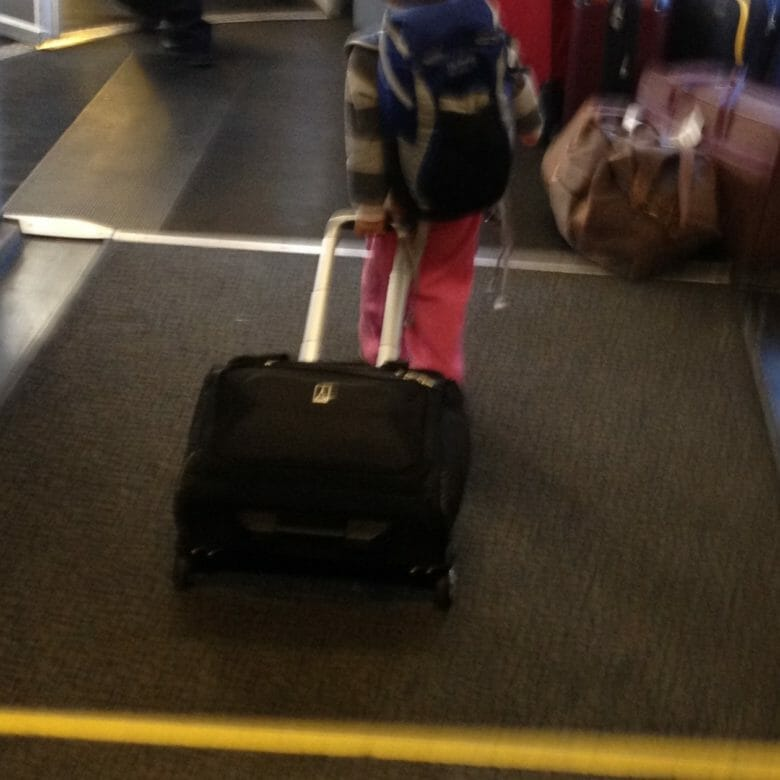 Essie, age three, boarding a plane last winter with her own luggage.